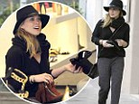 For the love of boots! Hilary Duff cover up from the rain in a fashionable black hat as she shops for boots in Beverly Hills
