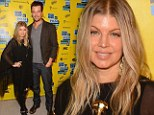 Finding a balance: Fergie covers up her growing baby bump in a flowing black tunic... but maintains her rocker chic edge in racy lace-up trousers
