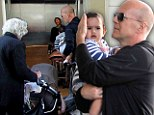 Caught in a pram jam! Bruce Willis shields baby Mabel Ray as he and his wife Emma Heming get caught in a pack of pushchairs