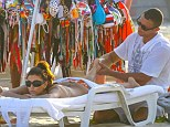 The luckiest masseur in the world! Eva Longoria gets a rubdown in Rio as she suns herself in a tropical printed bikini