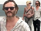 Bristling with happiness: Joaquin Phoenix shows off his new mutton chops beard on a romantic stroll with his girlfriend