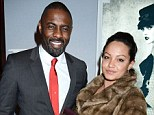 Dapper: Idris Elba poses up with a mystery brunette at the Harrods event - he looks almost happier than her
