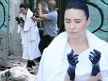 Demi Lovato slums it in a rubbish strewn alleyway with her hands dipped in black paint as she films her new video