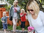 Stopping and smelling the roses! Busy mother Naomi Watts picks up fresh flowers before taking a stroll with her children