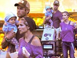Putting those muscles to good use! Thor star Chris Hemsworth holds on tight to little baby India on a shopping trip