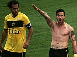 Sparking a storm: Giorgos Katidis raises his hand in a Nazi-style salute, as his teammate Roger Guerreiro looks on