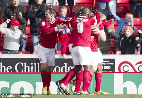 Tykes triumph: Bobby Hassell is mobbed by Barnsley teammates