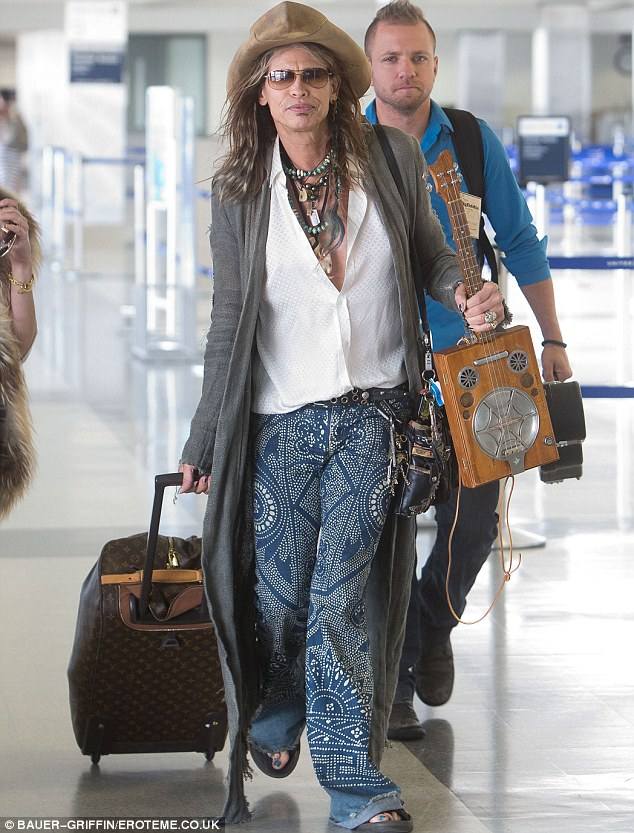 Signature style: Steven Tyler, 64, walked through LAX on Friday with a custom ukulele in tow and sporting some unique duds