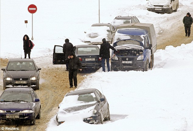 Stranded motorists wait near their vehicles in Minsk as much of Eastern Europe battles with heavy snow