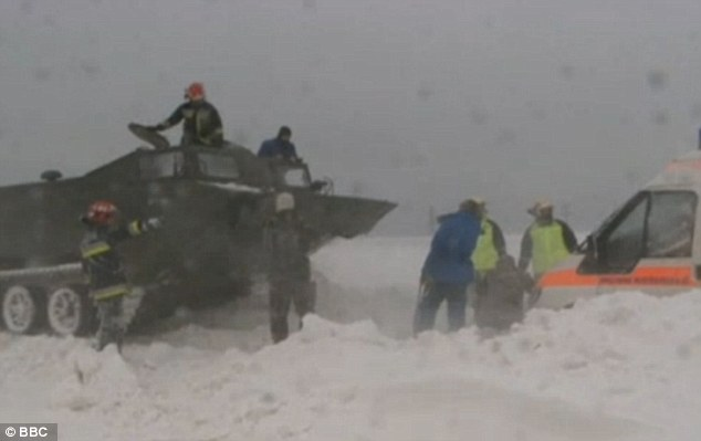 Tanks a lot: Hungarian soldiers use a military vehicle to pull trapped motorists from a snowdrift