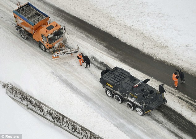 Rescue: Police use a tank to pull a stranded snowplough as bad weather in Hungary and across much of Eastern Europe caused travel chaos