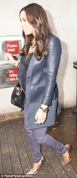 Still in her skinnies: The 23-year-old slipped into a pair of jeans as she concealed her bump under a black top