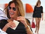 Cocktail hour! Kelly Bensimon shows off her amazing bikini body while enjoying a pina colada on the beach