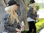 Is that you, Christina Aguilera? The usually glamorous singer looks disheveled as she hides her scraggly tresses under a baseball cap