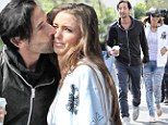 Adrien Brody showers model girlfriend with kisses... but she doesn't seem to be in the mood for a public display of affection