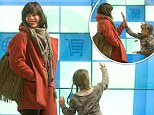 Game on: Milla Jovovich and daughter Ever occupy themselves at baggage reclaim with fun panel game