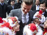 Thrilled: David was embraced by a number of youngsters wearing traditional Chinese dress