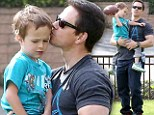It's never too early to learn! Mark Wahlberg showers son Brendan with affection as he teaches him how to throw a football