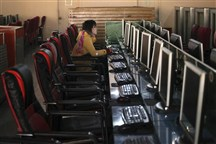 A woman uses a computer in an Internet cafe.
