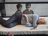 Living art: Two young boys peer in on actress Tilda Swinton who's currently sleeping in a glass display case at the MoMA this month in New York