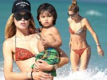 Model behaviour! Doutzen Kroes works on her tan in a colourful animal print bikini while looking after son at the pool