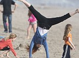 Active mum: Marcia Cross did cartwheels across the beach in Santa Monica on Monday with twin daughters Eden and Savannah
