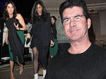 Simon Cowell shows off his reading glasses as he's joined on night out by two ladies