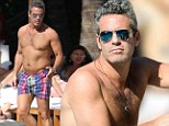 Blue steel: TV Host Andy Cohen, 44, looks tan and trim poolside in Miami