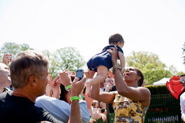 First Lady Michelle Obama lifts a baby at Easter Egg Roll