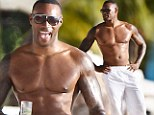 'Ridiculously good looking' supermodel and Zoolander star Tyson Beckford shows off his impressive muscles as he hits the beach in Barbados