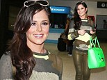There's no hiding in that outfit! Cheryl Cole teams her camouflage jumper with skintight gold trousers and a neon green bag