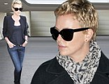 It's all in the jeans! Charlize Theron shows off her stunning figure and long legs in skin-tight denim as she jets into LAX