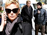 Charlize Theron is effortlessly chic as she towers over a male friend while on lunch date