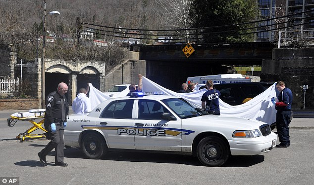 Crime scene: Law enforcement officers and emergency service personnel cover the vehicle at the scene of the shooting in downtown Williamson with one suspect in custody
