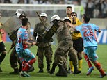 Violence: Arsenal players clash with riot police who came onto the pitch to protect the referee