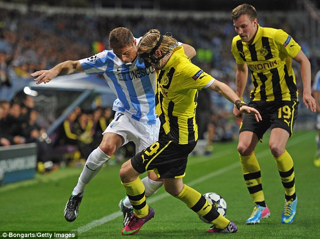Battle for the ball: Marcel Schmelzer challenges for the ball with JoaquÌn of Malaga