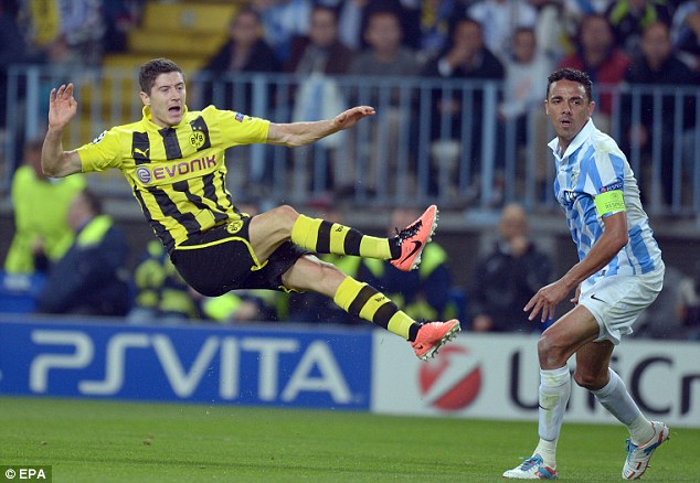 Flying through the air: Dortmund's Robert Lewandowski and Malaga's Weligton vie for the ball