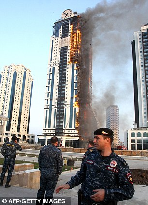 Blaze: Officers cordon off the area around a skyscraper, which is part of the Grozny-City complex, on fire in the Chechen capital Grozny