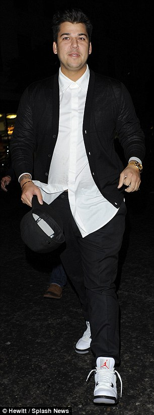 Stylish guy: Rob looked smart in black trousers and a loose white shirt as he smiled while walking to the restaurant