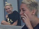 Miley Cyrus takes a drag of a suspicious looking hand-rolled cigarette on her hotel balcony in Miami