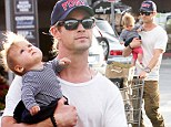 Talk about multitasking! Human stroller Chris Hemsworth takes it to a new level by pushing shopping trolley AND holding baby
