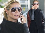 Hanging on the telephone: Heidi Klum keeps her cell close as she touches down without her bodyguard boyfriend Martin