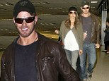 Incognito love: Kellan Lutz and girlfriend Sharni Vinson try to keep a low profile as they fly into Los Angeles