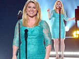 A size too small? Kelly Clarkson's light blue lace dress bunches around her waistline as she takes to the stage at ACM Awards