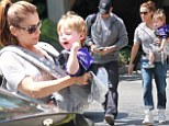 All in the family! Alyssa Milano enjoys a sporty Saturday with her boys as she carries her son to the Kings game