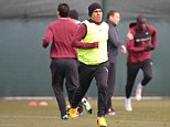 Bib of a different kind: Tevez wore a hi-vis vest as he started clearing out a 30ft unit