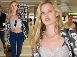 Georgia May Jagger flashes her toned stomach in a crop top and low-slung skinny jeans as she touches down in Australia