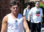Zac Efron shows guns whilst Seth Rogen covers up