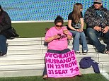 Fed up: A woman attending Wrestlemania 29 in New Jersey last Sunday brought with her a bright pink sign calling out the exact seat and row of out her cheating husband