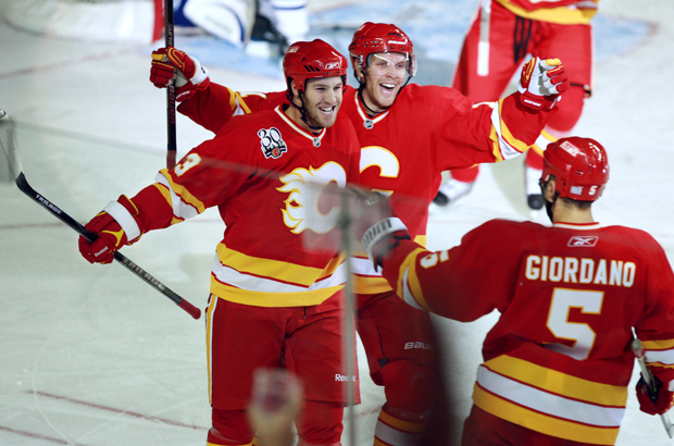 Calgary Flames players, from left, centre Brandon Prust, right winger Fredrik Sjostrom and defenceman Mark Giordano celebrated after Prust scored the Flames fourth goal against the Vancouver Canucks during the second period of their season opener on October 1, 2009 at the Pengrowth Saddledome in Calgary, AB